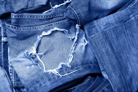 Macro texture of jeans hole and threads colored in classic blue.