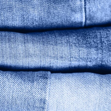 Stack of jeans on table. classic blue color. color of year 2020. Ecology and recycling.