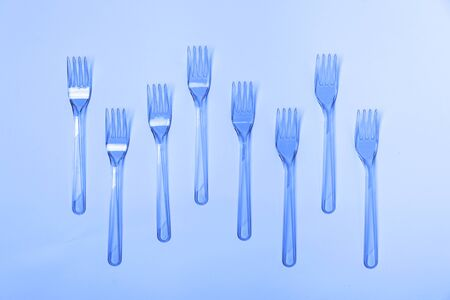 Plastic fork pattern on classic blue background. Concept of color 2020.
