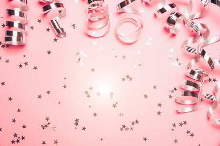 Pink confetti and golden stars and sparkles on pink background. Top view, flat lay. Copyspace for text. Bright and festive holiday background. For Christmas, New year, Mothers day.