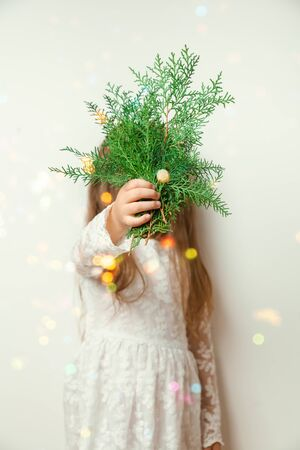 Cute happy little girl Laughing in Christmas atmosphere with gift boxes and magic lights. Happy child holding spruce branch.
