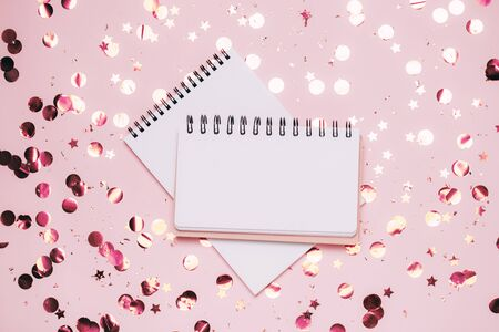 Empty note pad on pastel pink confetti background. Top view, flat lay. Holiday and festive Christmas mock up.