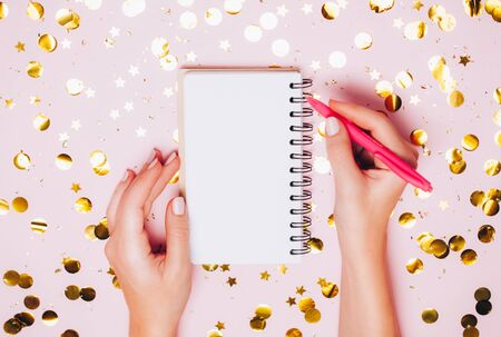 Female hands holding notebook with empt copy space on festive confetti background. Top view, flat lay. Christmas greeting card.