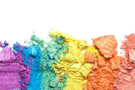 A broken rainbow colored eye shadow smear, make up palette isolated on a white background. Top view, flat lay. Holographic neon colors.