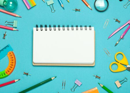 Colorful pink background with various School accessories and stationery are laid out in the form of a rainbow. Empty notebook, mock up. Flat lay top view. Imagens