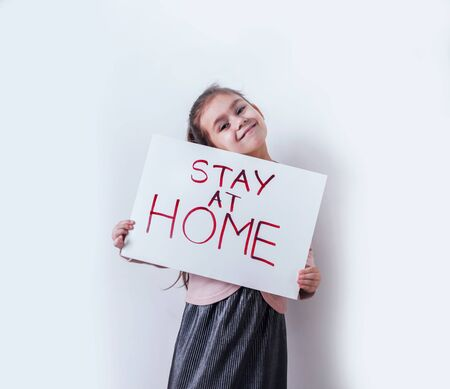 Little girl holding in hands poster with Stay at home word.