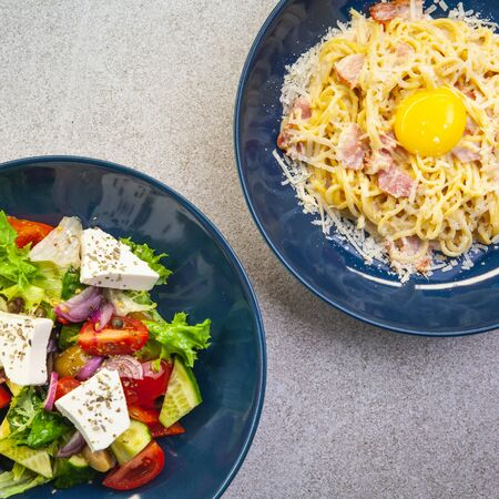 Pasta carbonara and Greek salad on grey table. top view, flat lay 写真素材