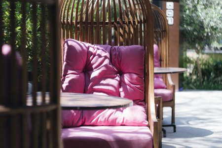 wicker chair with pink pillows on a summer veranda in a cafe