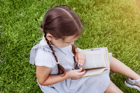 Cute schoolgirl with pigtails laying on grass while reading book.