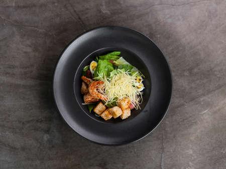 Caesar salad with shrimps in black plate