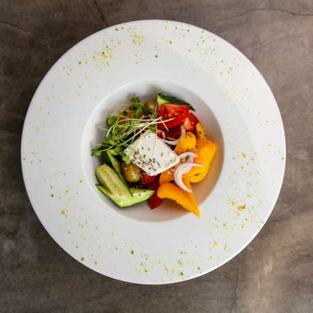 Greek salad in white plate on grey table.