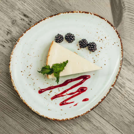 Cheesecake with blackberry on beautiful plate.