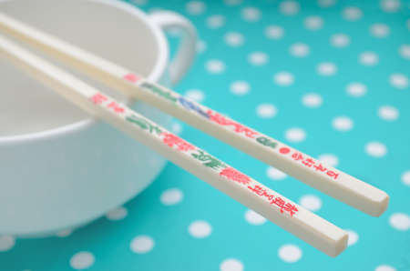 take a history: two chopsticks with hieroglyphics on the green background Stock Photo