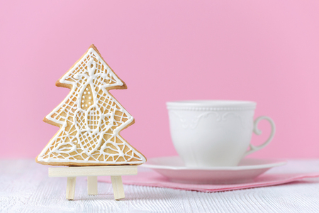 christmas tree gingerbread on the painting easel with coffe cup on pink background