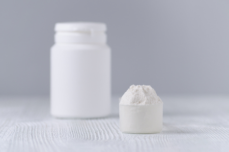 a scoop with white powder closeup and a jar on gray background