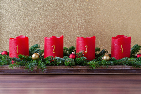 traditional red advent candles with numbers and branch of fir with christmas baubles on gold background
