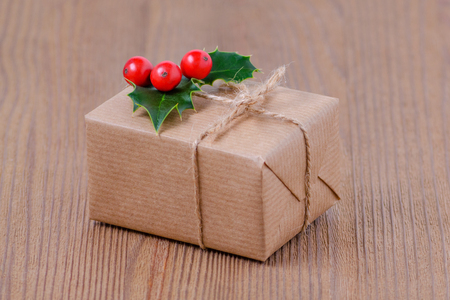 gift box with holly berries on wooden background, selective focus