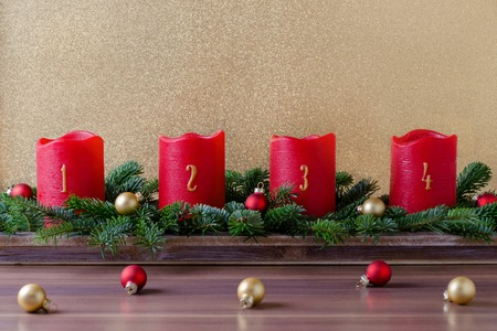 traditional red advent candles with numbers and christmas decoration, branch of fir with baubles on gold background