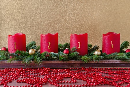 traditional red advent candles with numbers and christmas decoration, branch of fir with garland on gold background