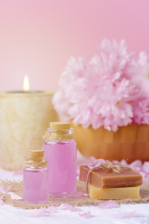 beautiful spa composition with massage oil, candle, soap bar and fresh pink flowers