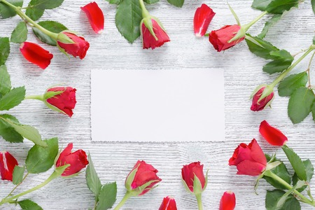 frame with red roses and white card for text on the vintage wooden background