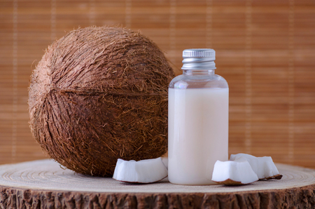 diy cosmetic bottle and fresh organic coconut , natural background