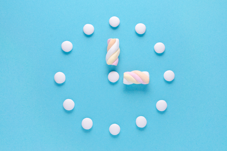 concept image, a clock with candy and marshmallow on blue background, flat lay Stockfoto