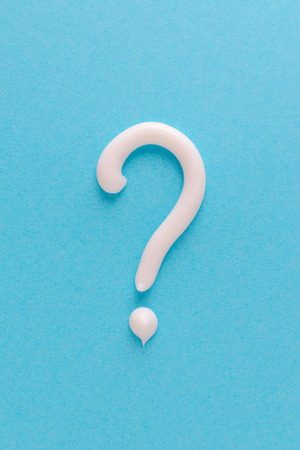 question mark from white toothpaste on blue background