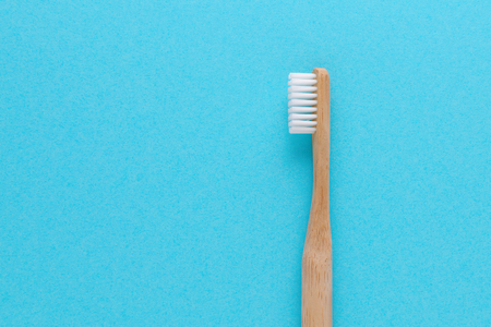 wooden toothbrush on blue background with copy space