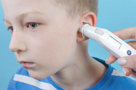 taking temperature with ear thermometer by child