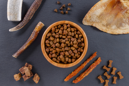 different dog food and snack, chicken filet, antlers, lung, ear on black background, top view