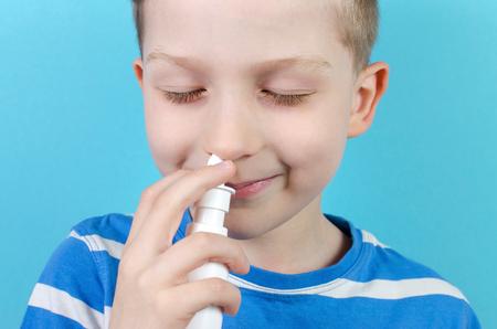 Retrato de niño sonriente con spray nasal, fondo azul. Foto de archivo