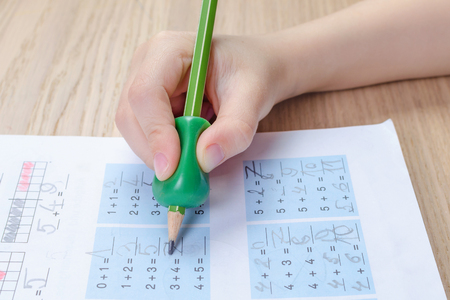 childs hand with writing tool for help by incorrect holding of pencil, homewortk, math Banco de Imagens