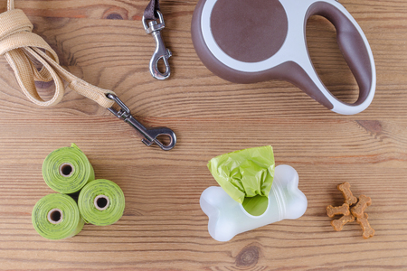 dog wolking equipment, leash, poop bags and treats on wooden background