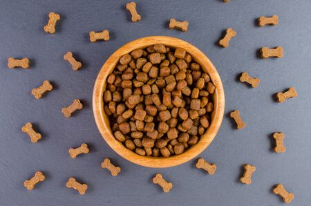 dog food in a wooden bowl and snack like bones on black background, flat lay Imagens
