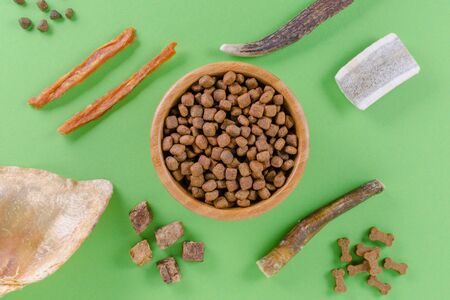 different dog food and snack, chicken filet, antlers, lung, ear on green background, flat lay