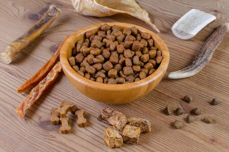 dried dog food in a bowl and different snack, chicken filet, antlers, lung, ear on wooden background, selective focus