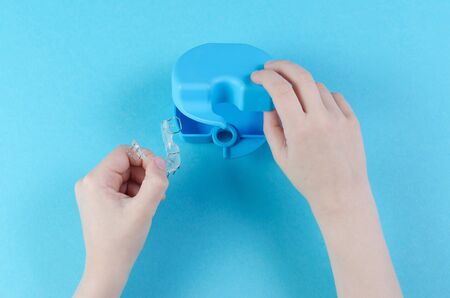 childs hand with orthodontic appliance with box on blue background