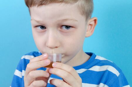 boy takes medicine syrup on blue background