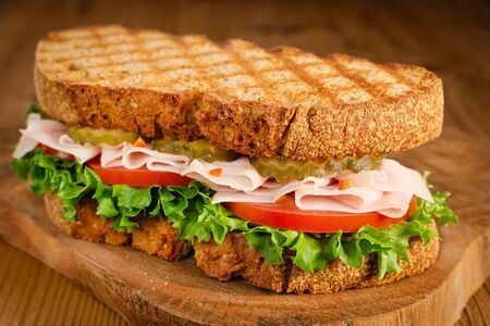 handmade tasty turkey sandwich with tomato, salad and cucumber, on wooden background
