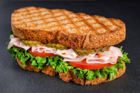 handmade tasty turkey sandwich with tomato, salad and cucumber, on black background Stock Photo