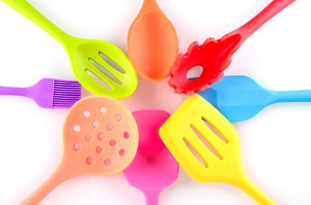 multi colored kitchen utensils on white background, flat lay