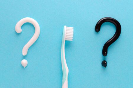 question from white and black toothpaste, teeth care concept, toothbrush on blue background Stock Photo