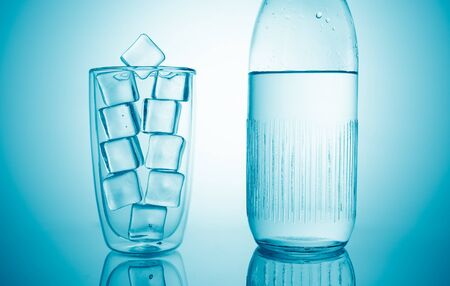 a glass with ice cubes and a bottle with fresh drink water on blue background