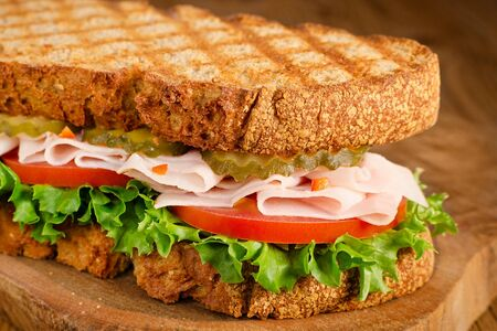 handmade tasty turkey sandwich with tomato, salad and cucumber, on wooden background, closeup