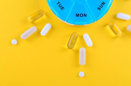 different medicines for one week and a pills box on yellow background with copy space