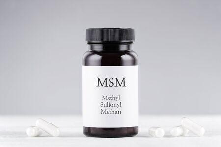 nutritional supplement msm, sulfur, methylsulfonylmethan bottle and capsules on gray Banco de Imagens - 133167438