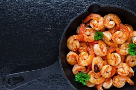 tasty roasted shrimps in a pan with parsley and garlic on black background, flat lay 스톡 콘텐츠