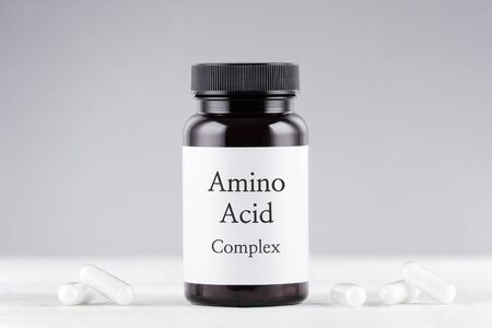 nutritional supplement amino acids bottle and capsules on gray