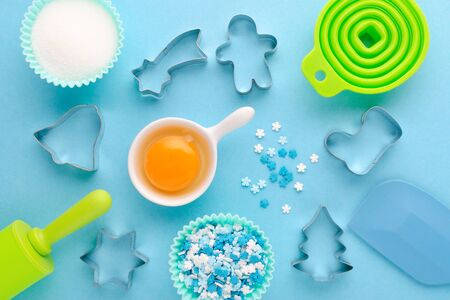 ingredients and kitchen tools for baking on blue background, flat lay